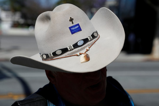 A man wears a pin on his cowboy hat in support of Republican U.S. presidential candidate Donald Trump during a campaign rally in San Jose, California