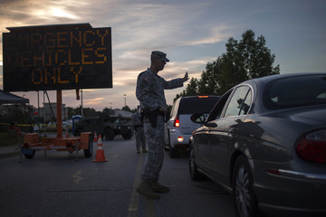 A member of the National Guard assists a commuter with directions while stands guard at a staging area inside a shopping center parking lot in Ferguson, Missouri