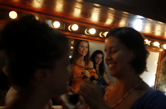 Actresses Carvalho and Gomide are reflected in a mirror as they apply make-up before their show at a local theatre in Rio de Janeiro