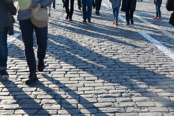 Pedestrians on cobblestone pavement, shadows, people traffic