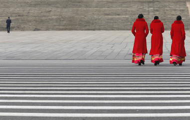 Hotel guides walk at Tiananmen Square near Great Hall of People during fourth plenary meeting of National People's Congress in Beijing