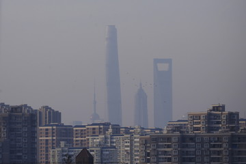 A view of Shanghai's skyscrapers, Oriental Pearl Tower (L), Shanghai Tower (2nd L), Jin Mao Tower (2nd R) and the Shanghai World Financial Center (R) are seen amid heavy smog in Shanghai