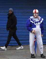 A man looks at a clown on his way to a service of remembrance in honour of British clown Joseph Grimaldi at All Saints Church in Haggerston in London