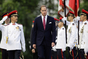 Britain's Prince William inspects an honour guard during a welcoming ceremony at the Istana in Singapore