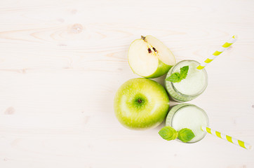 Decorative border of green apple fruit smoothie in glass jars with straw, mint leaves, cut apples, top view. White wooden board background, copy space.