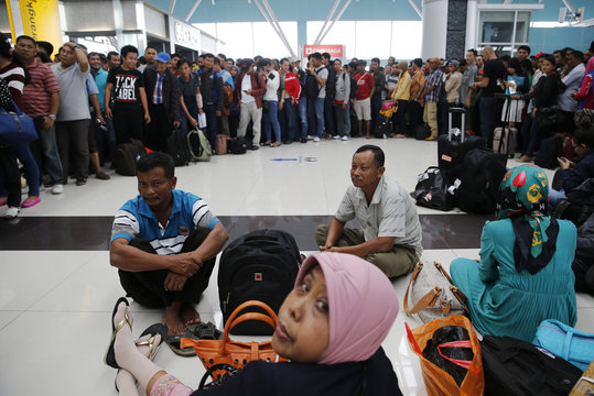 Lion Air passengers stand in a line to claim their tickets money back after their flights were delayed at Soekarno-Hatta airport in Jakarta