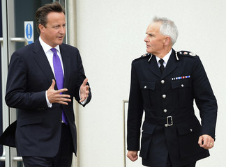 Britain's Prime Minister David Cameron speaks with the Chief Constable of Greater Manchester Police, Peter Fahy, during his visit to their headquarters in Manchester