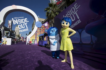 """Joy"" and ""Sadness"", characters of the animation film ""Inside Out"", pose at its premiere at El Capitan theatre in Hollywood"