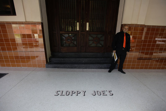 A porter stands at the entrance of newly reopened Sloppy Joe's bar in Havana