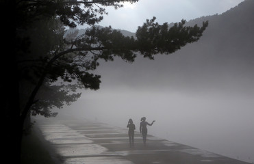 People walk along a foggy embankment of the Yenisei river in the Siberian town of Divnogorsk
