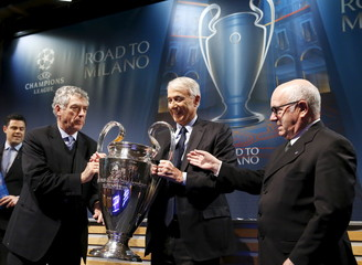 UEFA Vice-President Villar Llona of Spain gives the trophy to Pisapia Mayor of Milano and Tavecchio Chairman of the Italian Football Association after the draw of Champions League semi finals in Nyon