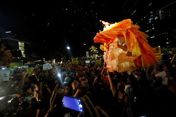 People hold a pinata which was lit on fire while protesting the election of Republican Donald Trump as the president of the United States in downtown Los Angeles