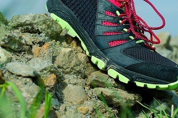 Trail running shoe on stony surface in action. Running concept.