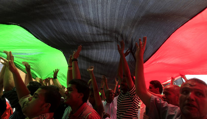 Libyans celebrate with a Kingdom of Libya flag after receiving the news of an arrest warrant issued against Muammar Gaddafi at the courthouse in Benghazi