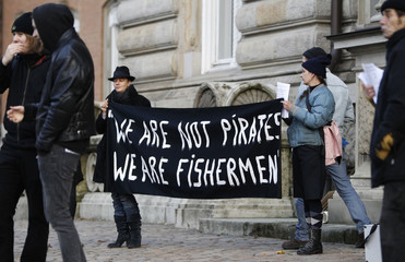Human rights activists protest outside court during trial against ten Somali men accused on piracy at criminal court in Hamburg