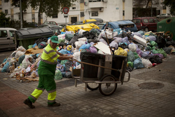 A street sweeper pushes his garbage cart past a pile of rubbish bags in a street during a strike in Jerez de la Frontera