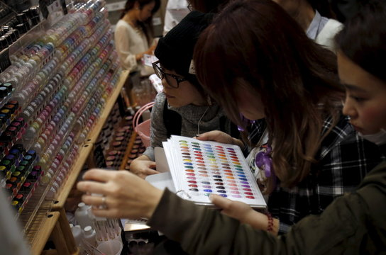 Shoppers look at various colors of manicure displayed at an exhibition and sale during Tokyo Nail Expo 2015 in Tokyo
