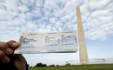 A woman holds up her tickets for the re-opening of the Washington Monument in Washington