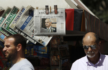 People walk in front of kiosk where Kathimerini newspaper featuring a photograph of Greek PM Papandreou is displayed in Athens
