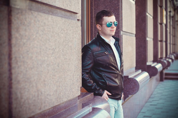 Young brunette man walk in center of city and European streets in leather black jacket and blue mirror sunglasses. Student meeting with friend and wait him