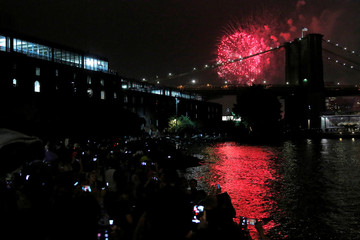 Fireworks explode behind the Brooklyn Bridge during the Macy's 4th of July Fireworks on the East River in New York, U.S.