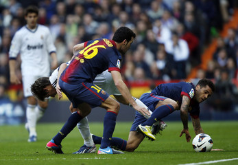 Real Madrid's Coentrao fights for the ball with Barcelona's Busquets and Alves during their Spanish first division soccer match in Madrid