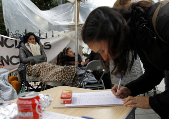 Supporter signs petition as disabled Carasquilla and Murcia sit in their wheelchairs, chained to bars, on the third day of their protest against the non-payment of their social subsidy since August, in Valencia