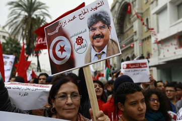 An activist holds a placard depicting a picture of government critic Mohamed Brahmi, who was gunned down last year, in Habib Bourguiba boulevard in Tunis