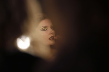 A model gets makeup applied on her during the Mercedes-Benz Fashion Week in Madrid
