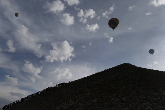 Hot air balloons float above people standing in line to climb the Pyramid of the Sun and welcome the spring equinox in the pre-hispanic city of Teotihuacan, on the outskirts of Mexico City