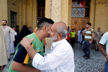 People greet each other after attending prayers at a Sunni mosque, during Eid al-Fitr as they mark the end of the fasting month of Ramadan, in Baghdad