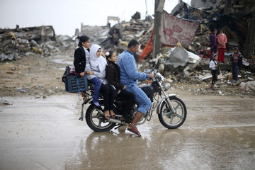 Palestinians ride a motorcycle past the ruins of houses in the east of Khan Younis