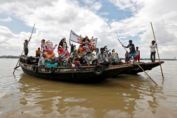 Idols of Hindu goddess Durga are transported on boats through the waters of river Ganga to pandals ahead of the Durga Puja festival in Kolkata