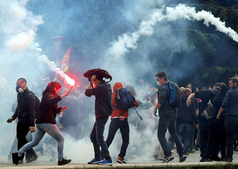 A protester carries a flare through teargas during a demonstration against French labour law reform in Nantes