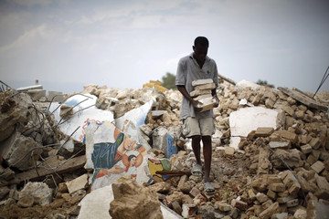 A man carries cinder blocks collected from rubble at a destroyed church in Port-au-Prince