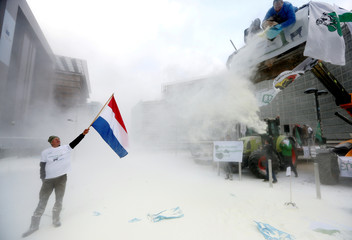 A milk producer waves a Dutch flag as farmers spray powdered milk to protest against dairy market overcapacity in Brussels