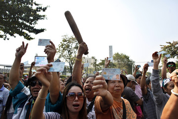 Protesters demanding the right to vote, hold up their identity cards and a rolling pin before a minor clash between supporters and opponents of Thailand's government outside a polling station in central Bangkok