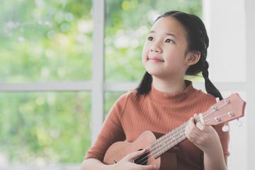 Beautiful Asian girl playing ukulele