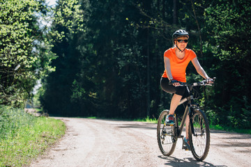 Young pretty woman in helmet and orange shirt riding a  bicycle on the forest road. Healthy lifestyle concept. Sports Girl with bike.