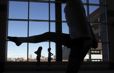 Dancers are silhouetted as they practice before competing in the World Irish Dancing Championships in Boston