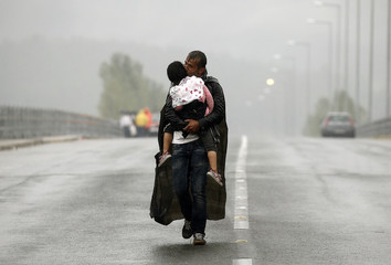A Syrian refugee carries his daughter through a rainstorm towards the Greek-Macedonian border