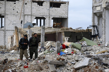 Fighters of the Kurdish People's Protection Units (YPG) stand on the debris of a damaged building in the northern Syrian town of Kobani