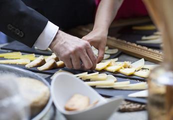 Hombre cogiendo queso en aperitivo
