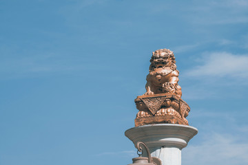 Statue of lion / Statue of chinese lion sitting with sunny on blue sky background.