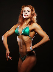 blond bodybuilder woman in bikin on black background