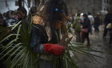A man wearing a costume carries sheep shears during carnival celebrations in Zubieta