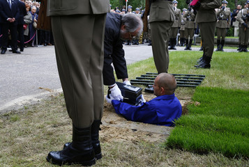 A man is handed the urn, containing the ashes of the late General Wojciech Jaruzelski, for burial during a funeral ceremony at Powazki military cemetery in Warsaw