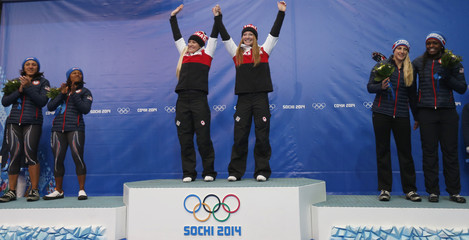 Canada's and U.S. teams celebrate during flower ceremony for women's bobsleigh event at 2014 Sochi Olympic Games