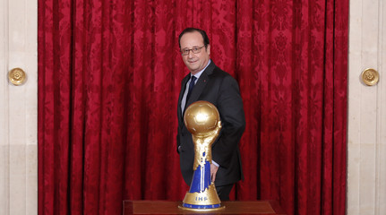 French President Francois Hollande poses next to the trophy during a meeting with members of the French national handball team at the Elysee Palace in Paris