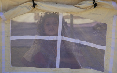 A flood victim looks out from her family tent at a relief camp for flood victims in Charsadda